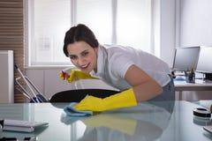 Szczęśliwy Żeński Janitor Cleaning biurko Z łachmanem obrazy stock