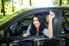 Szczęśliwy żeński kierowca pokazuje samochodu klucz w jej nowym samochodzie obraz royalty free