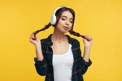 Szczęśliwy żeński nastolatek cieszy się dźwięka muzyka, trzyma jej koników ogony, zakończenia one przyglądają się od przyjemności obrazy royalty free