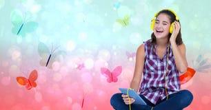 Szczęśliwy żeński słuchanie muzyka przez hełmofonów używać pastylka peceta nad motylim tłem Obraz Stock