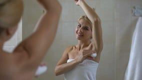 Szczęśliwy żeński stosować antiperspirant i patrzeć w łazienki lustrze, higiena zdjęcie wideo