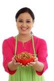 Szczęśliwy żeński szef kuchni trzyma puchar migdały przeciw bielowi Zdjęcia Stock