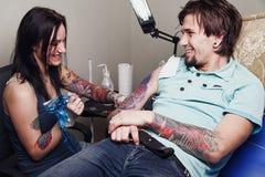 Szczęśliwy żeński tatuażu mistrz i dorosły mężczyzna Fotografia Royalty Free