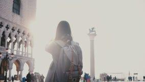 Szczęśliwy żeński turysta bierze smartphone fotografie zadziwiać San Marco kwadrat w Wenecja Włochy z światło słoneczne obiektywu zbiory wideo