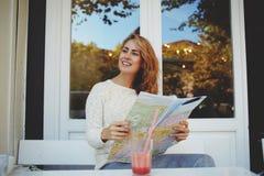 Szczęśliwy żeński turysta siedzi w wygodnej chodniczek kawiarni podczas weekendowego relaksu z lokaci mapą w rękach, Obrazy Royalty Free