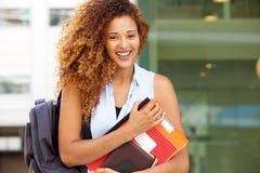 Szczęśliwy żeński uczeń ono uśmiecha się z torbą i książkami na kampusie zdjęcia stock
