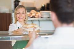 Szczęśliwy żeński wlaściciel sklepu daje kanapce klient Obrazy Stock
