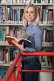 Szczęśliwy Żeńskiego ucznia czytanie od książki w bibliotece obrazy royalty free