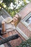 Szczęśliwy żeńskiego ucznia obsiadanie na ławce Zdjęcie Royalty Free
