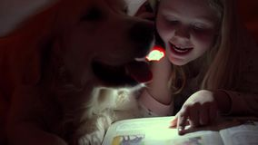 Szczęśliwy życie z zwierzętami domowymi - małe dzieci czyta książkę pod pokrywami z ich dużym psem przy nocą zbiory wideo