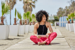 Szczęśliwy afro amerykański kobiety obsiadanie krzyżujący iść na piechotę słuchającą muzykę o Zdjęcie Stock