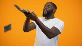Szczęśliwy afroamerykański mężczyzna rzuca dolarów banknoty, marnotrawi pieniądze, pojęcie zbiory