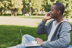 Szczęśliwy afroamerykański studencki używa laptop w parku fotografia royalty free