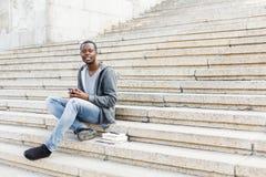 Szczęśliwy afroamerykański studencki używa smartphone outdoors fotografia royalty free
