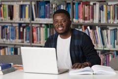 Szczęśliwy Afrykański Męski uczeń Z laptopem W bibliotece Obrazy Royalty Free