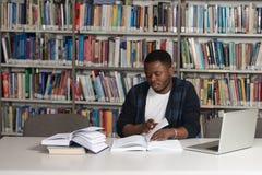 Szczęśliwy Afrykański Męski uczeń Z laptopem W bibliotece Zdjęcia Stock