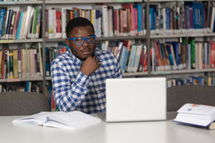 Szczęśliwy Afrykański Męski uczeń Z laptopem W bibliotece Zdjęcie Stock