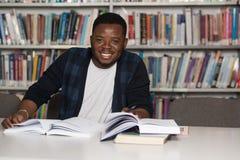 Szczęśliwy Afrykański Męski uczeń Z laptopem W bibliotece Fotografia Stock