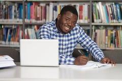 Szczęśliwy Afrykański Męski uczeń Z laptopem W bibliotece Obraz Stock