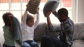 Szczęśliwy afrykański rodzinny tata i małe dzieci cieszy się poduszki walkę zbiory