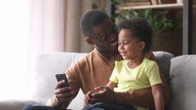 Szczęśliwy afrykański tata i mały syn śmia się patrzejący telefon zdjęcie wideo