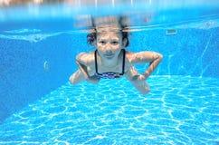 Szczęśliwy aktywny podwodny dziecko pływa w basenie Zdjęcia Stock