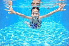 Szczęśliwy aktywny podwodny dziecko pływa w basenie Zdjęcie Stock