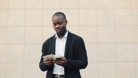 Szczęśliwy amerykanin afrykańskiego pochodzenia biznesmen trzyma dużą kwotę pieniądze w jego ręki Stoi w ulicie blisko biura zbiory