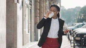 Szczęśliwy amerykanin afrykańskiego pochodzenia bizneswoman słucha muzyka w hełmofonach na smartphone, chodzi na zewnątrz biura i zbiory wideo