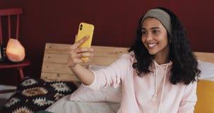 Szczęśliwy amerykanin afrykańskiego pochodzenia dziewczyny obsiadanie na łóżku przy homec hatting z jej przyjaciółmi na wideo wzy zbiory