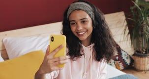 Szczęśliwy amerykanin afrykańskiego pochodzenia dziewczyny obsiadanie na łóżku przy homec hatting z jej przyjaciółmi na wideo wzy zbiory wideo