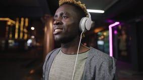 Szczęśliwy amerykanin afrykańskiego pochodzenia mężczyzna jest ubranym hełmofon przy nocy podziemnym miejscem