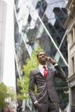 Szczęśliwy amerykanina afrykańskiego pochodzenia biznesmen używa telefon komórkowego na zewnątrz budynku Fotografia Stock