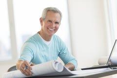 Szczęśliwy architekta mienia projekt Przy biurkiem Zdjęcie Royalty Free