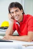 Szczęśliwy architekta obsiadanie biurkiem Zdjęcie Royalty Free