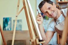 Szczęśliwy artysta ono uśmiecha się w obrazu studiu zdjęcia stock