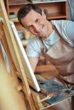 Szczęśliwy artysta pozuje w obrazu studiu obrazy stock