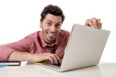 Szczęśliwy atrakcyjny biznesmen w koszula i krawacie przy biurowym biurkiem pracuje z komputerowy ono uśmiecha się Fotografia Royalty Free