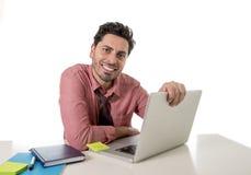 Szczęśliwy atrakcyjny biznesmen w koszula i krawacie przy biurowym biurkiem pracuje z komputerowy ono uśmiecha się Obrazy Royalty Free