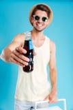 Szczęśliwy atrakcyjny młody człowiek daje ci butelce soda zdjęcia stock