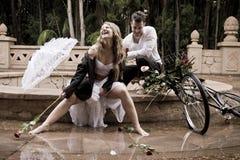 Szczęśliwy atrakcyjny pary obsiadanie przy krawędzią fontanna z rocznik różami i bicyklem zdjęcia stock