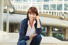 Szczęśliwy atrakcyjny starej kobiety siedzący outside w mieście zdjęcie stock