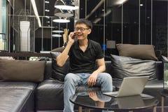 Szczęśliwy Azjatycki biznesmen opowiada na laptopie w livin i telefonie zdjęcia stock