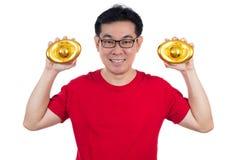 Szczęśliwy Azjatycki Chiński mężczyzna jest ubranym czerwonego koszulowego trzyma ingot Obraz Stock
