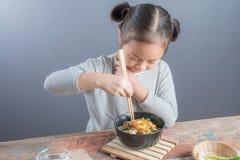 Szczęśliwy Azjatycki dziecko je wyśmienicie kluski obrazy royalty free