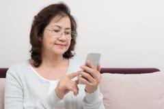 Szczęśliwy Azjatycki starszy kobiety obsiadanie na kanapie i używać mądrze telefon Zdjęcie Royalty Free