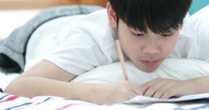 Szczęśliwy azjatykci śliczny chłopiec ręki mienia ołówek i writing twój praca domowa w domu zdjęcie wideo