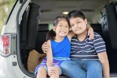 Szczęśliwy azjatykci dziecko siedzi w samochodzie, fotografia royalty free