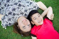 Szczęśliwy azjatykci dziecko z macierzystą sztuką outdoors w parku Obrazy Royalty Free