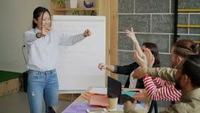 Szczęśliwy azjatykci dziewczyna taniec i odświętność sukces początkowy projekt pięć z wielo- etniczną drużyną wewnątrz i dawać wy zbiory